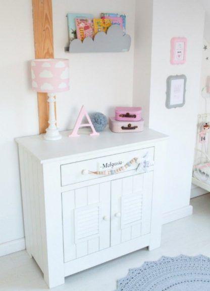 Lampa na białej komodzie z różowym abażurem