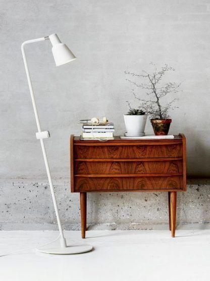 lampa podłogowa z cienką nóżką na betonowej ścianie