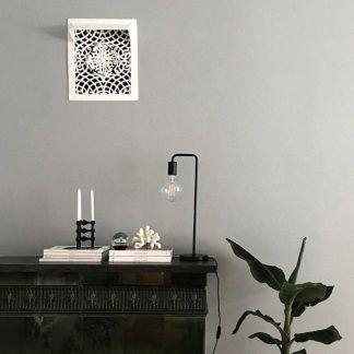 Czarna lampa stołowa na ciemnej komodzie