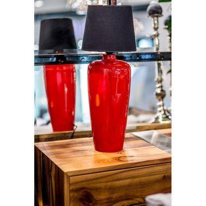 lampa stołowa z czarnym kloszem i czerwoną podstawą na drewnie
