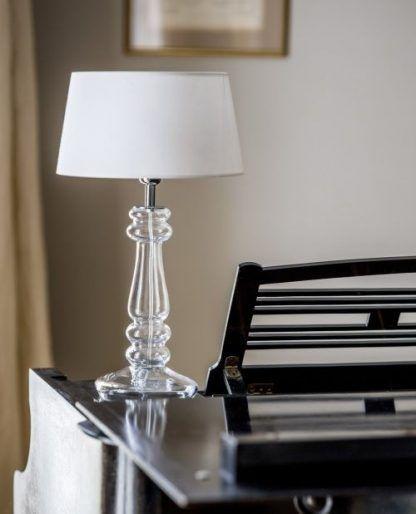 lampa stołowa ze szklaną podstawa i białym abażurem na stół