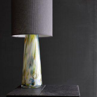 Lampa szklana w cętki na stoliku na tle szarej ściany