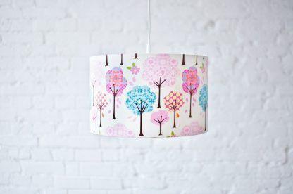 Lampa wisząca w pastelowe drzewa na tle białej ściany