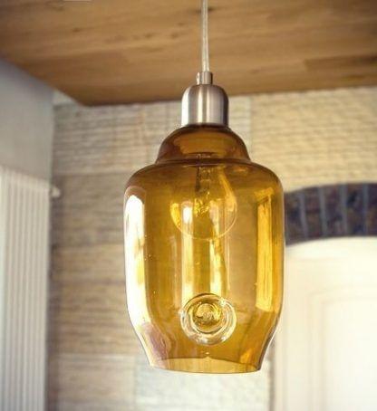 lampa wiszaca z miodowego szkła na drewnianym suficie