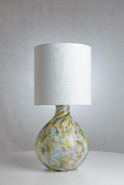 Lampa z białym abażurem ze szklaną podstawą w cętki