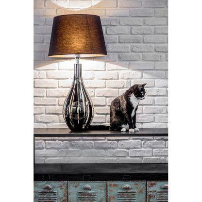 lampa z czarnym abażurem do komody na ścianie z cegły