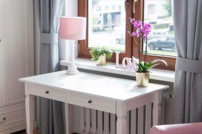Lampa z różowym abażurem na białym stoliku