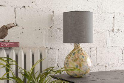 Lampa z szarym abażurem i podstawą w cętki w aranżacji jadalni