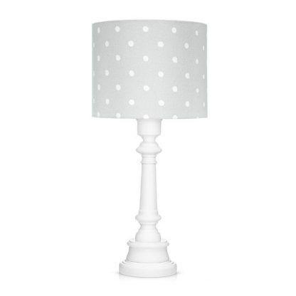 Lampa z szarym abażurem w kropki i białą podstawą