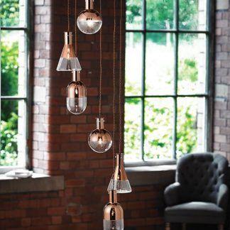 Lampa z sześcioma kloszami na tle murowanej ściany