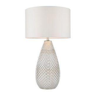 Lampa z wysoką szklaną podstawą i białym abażurem