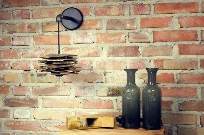 Lampa ze stalową rurką nad stolikiem ceglana ściana
