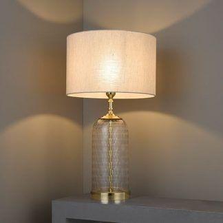 Lampa ze szklaną podstawą i złotym wykończeniem na stole