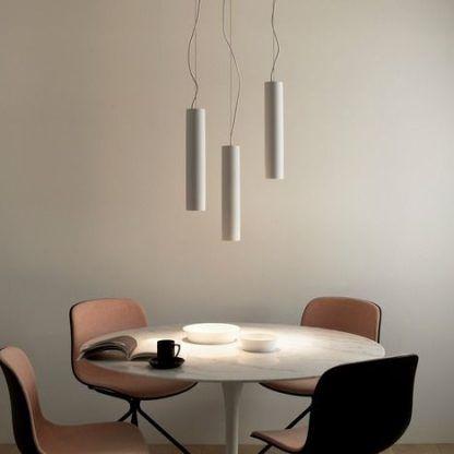 Lampy podłużne wiszące nad stołem w beżowej aranżacji