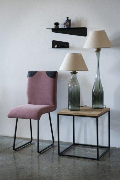Lampy szklane na stoliku na tle ceglanej ściany