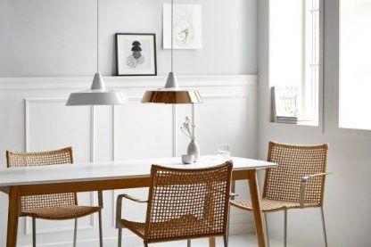 lampy wiszące nad białym stołem w jadalni - miedziana i biała