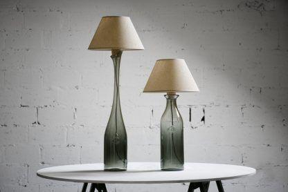 Lampy z szarą podstawą i abażurem na tle betonowej ściany
