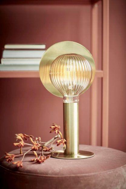 Metalowa złota lampa w bordowej aranżacji