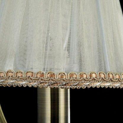metalowy kinkiet z kremowym abażurem do sypialni