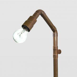 miedziana lampa z rur i żarówka ozdobna