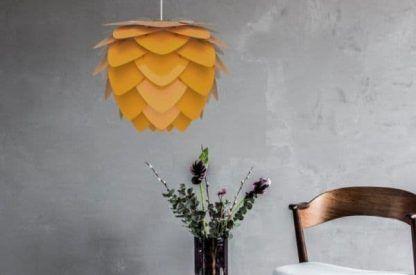 miodowa lampa wisząca na betonowej ścianie