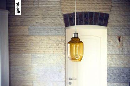 miodowa lampa wiszaca na marmurowej ścianie