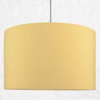 Musztardowa lampa wisząca na tle białej ściany