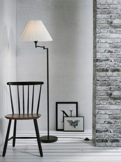 nowoczesna lampa podłogowa do szarej ściany z cegły w salonie
