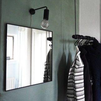 Nowoczesny czarny kinkiet wiszący nad lustrem