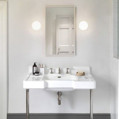 Okrągłe kinkiety w aranżacji białej łazienki