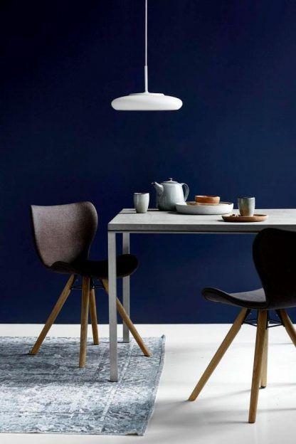 płaska lampa wisząca biała do granatowej ściany w salonie ze stołem