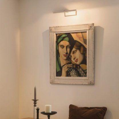 podłużny srebrny kinkiet nad obraz w salonie