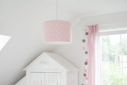 Różowa lampa w grochy wisząca w jasnym pokoju