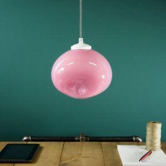 różowa lampa wiszaca okragła na zielonej ścianie