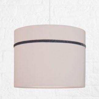Różowa okrągła lampa wisząca na tle białej ściany