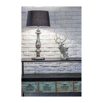 srebrna lampa stołowa na ceglanej ścianie