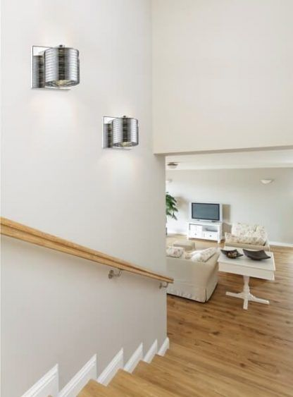 Srebrne kinkiety w białej aranżacji klatki schodowej