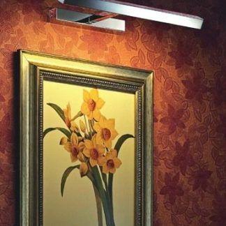 Srebrny kinkiet dekoracyjny oświetlający obraz na ścianie