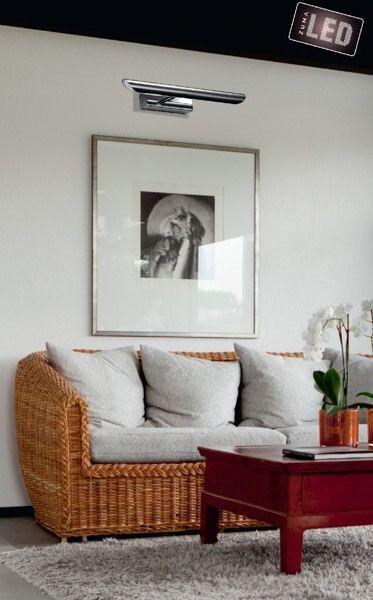 Srebrny kinkiet oświetlający obraz nad kanapą