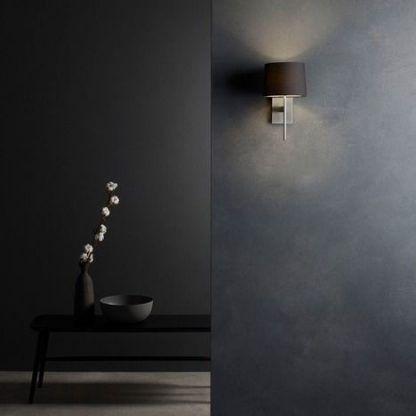 srebrny kinkiet z czarnym abazurem na ciemnej szarej ścianie
