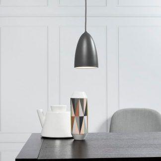 szara lampa skandynawska nad czarnym stole do białych ścian