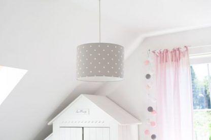 Szara lampa w białe grochy w jasnej aranżacji ścian