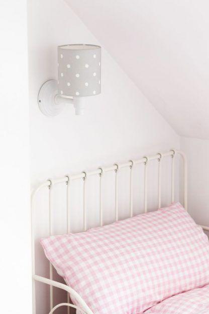 Szary kinkiet w białe grochy nad łóżkiem w sypialni