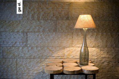 Szklana lampa na stoliku z plastrów drewna jasna ściana