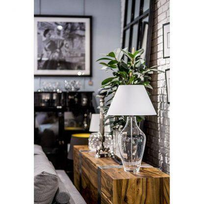 szklana lampa stołowa przezroczysta na drewnianej komodzie