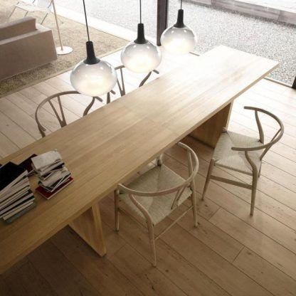szklana lampa wisząca nad drewnianym stołem