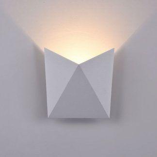 zapalony kinkiet designerski na białej ścianie - jak wygląda