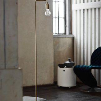 Złota lampa podłogowa na drewnianej podłodze