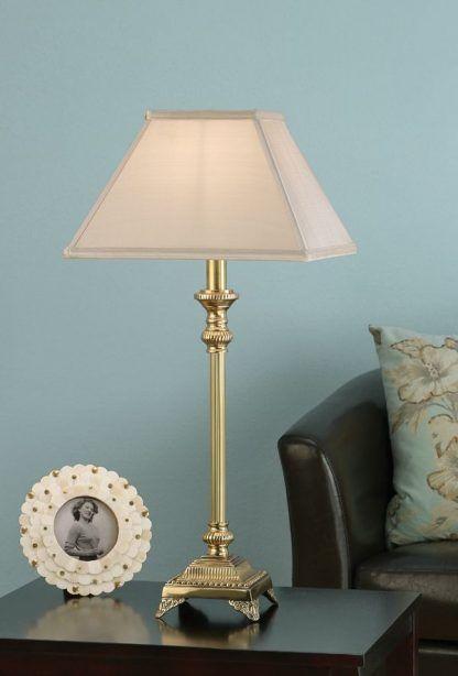złota lampa stołowa na błękitnym tle dekoracyjna