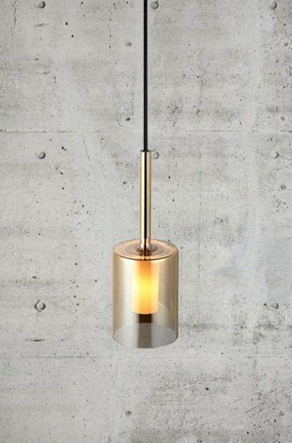 złota lampa wisząca na betonowej ścianie